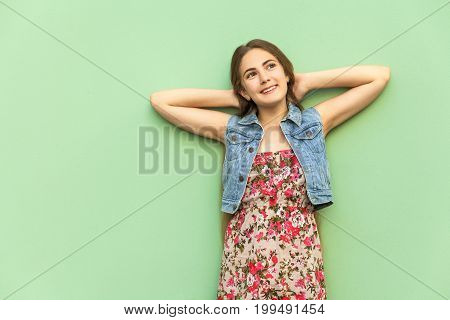 The beautiful long-haired blonde girl in flower dress having fun crossed hands onder head front of the light blue wall. Isolated studio shot.