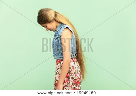 Side view of sad teenager girl punished alone at green wall. Indoor studio shoot