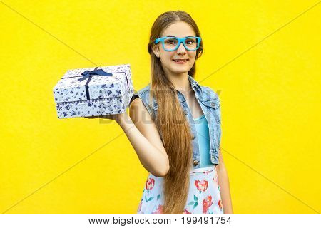 Portrait of a happy hipster smiling girl in dress and blue glasses holding present box and toothy smile isolated over yellow background. Indoor studio shoot