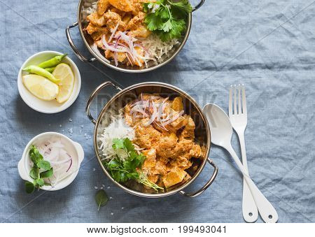 Vegetarian potato and cauliflower curry with rice in curry dishes on a blue background top view. Vegetarian healthy food concept. Flat lay