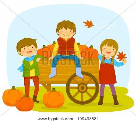 Kids with a cart of pumpkins during autumn.