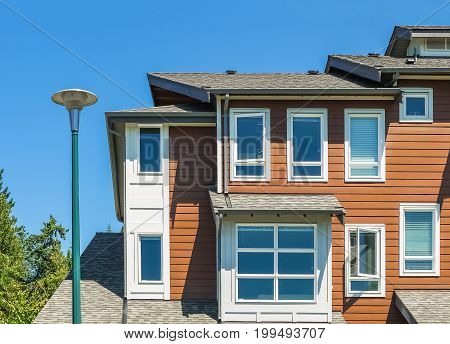 Corner of new townhouse unit with street light pole in front on blue sky background