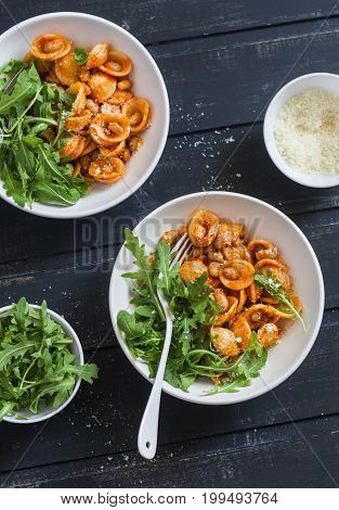 Pasta with beans tomato sauce parmesan and arugula on dark background top view. Vegetarian beans orecchiette pasta