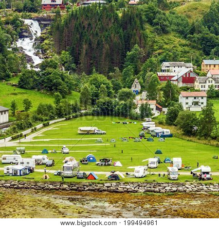 Tourist camping in Norwegian rural town Geiranger in summer season.