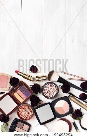 Various cosmetic products for make-up with rose flower on a white wooden background with copy space view from above. Decorative cosmetics female accessory makeup.