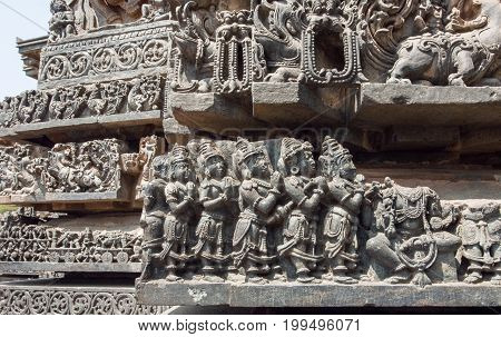 Ancient praying people on old wall of Hindu temple. Sculpured stone relief carvings from the 12th century temple in Karnataka. Old Indian artwork.