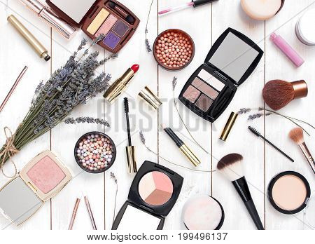 Various cosmetic products for make-up with lavender on a white wooden background top view. Decorative cosmetics female accessory makeup.