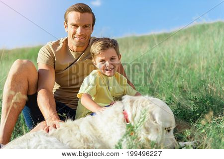 Portrait of cheerful father and son having fun with their Labrador pet on grassland. They are stroking the animal while looking at camera and laughing