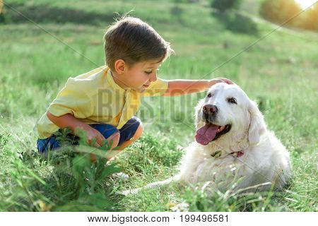 My lovely puppy. Kind little boy is stroking his Labrador with love. He is sitting on grass and smiling