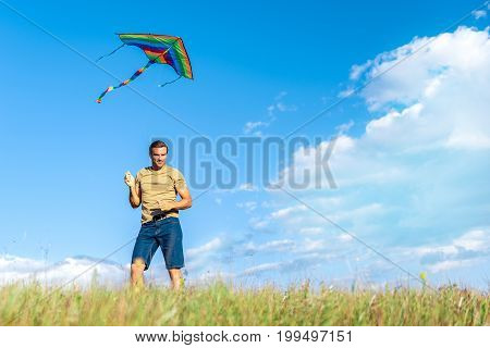 Full length portrait of happy young man launching a kite to the sky while standing on meadow. He is smiling. Copy space in right side. Low angle