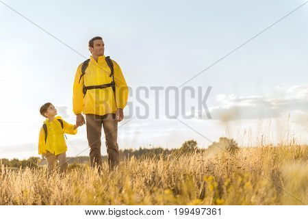Full length portrait of happy father and son in yellow raincoats walking on meadow with backpacks. They are holding hands and smiling. Copy space in right side