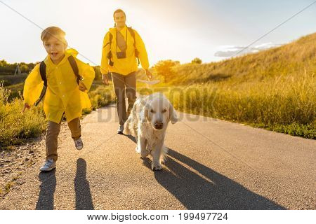 Forward to new adventures. Portrait of excited boy running on the road near his dog and daughter. He is laughing. Beautiful meadow around them
