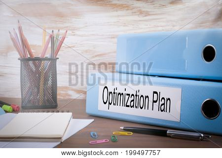 Optimization Plan, Office Binder on Wooden Desk. On the table colored pencils, pen, notebook paper.