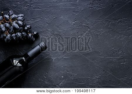 Bottle of wine and grape on black stone table background top view.