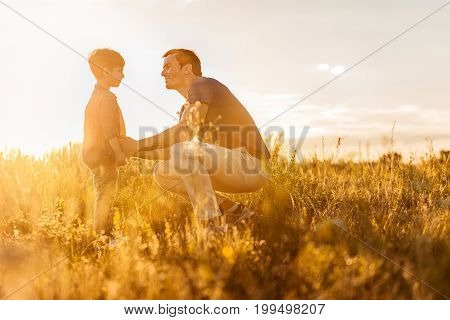 I love you, my son. Kind man is going to embrace his child while kneeling on grass. He is smiling and looking at boy with proud