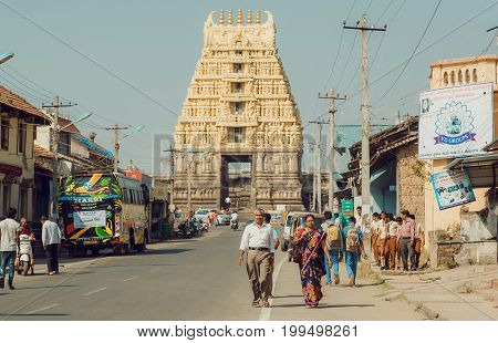 BELUR, INDIA - FEB 23, 2017: Walking people and vehicles past 12th century Chennakeshava Temple with carved tower gopuram on February 23, 2017. Population of Karnataka state is 62000000 people