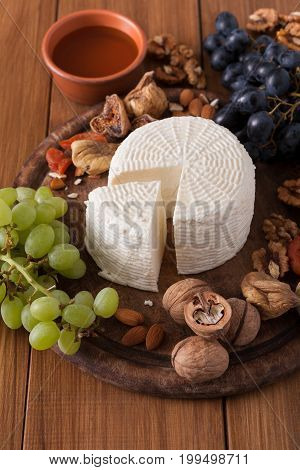 Cheese platter with fruits, homemade indian paneer cheese on wooden board with grapes and nuts, vertical