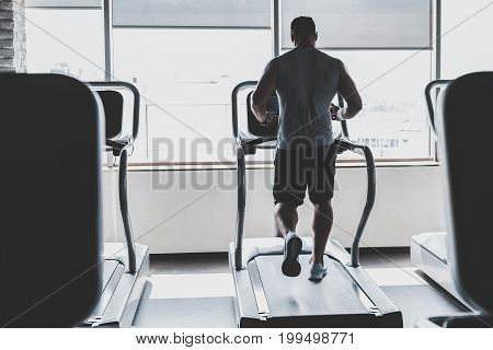 Full length strong-arm man making cardio. He doing sport while turning back to camera