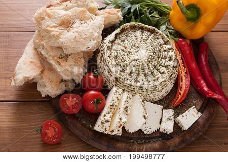 Homemade indian soft cheese paneer with herbs on wooden board with fresh vegetables and bread.
