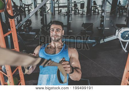 Top view portrait of unshaven athlete showing happiness while taking exercise in modern keep-fit studio