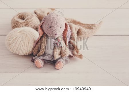 Vintage toy. Cute handmade rabbit with wool close up. Plush thing with materials of it, copy space. Creativity, handicraft, hobby concept