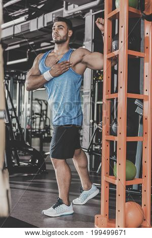 Low angle full length portrait of serene young unshaven man practicing sport in comfortable keep-fit studio. He standing near equipment