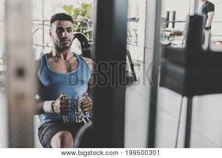 Portrait of bearded athlete expressing seriousness while practicing on thrust lower unit. Copy space
