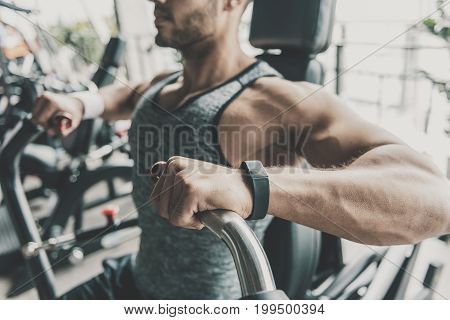 Close up male arms doing exercise on hammer simulator in keep-fit studio. Sport concept
