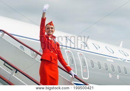 Charming Stewardess Dressed In Red Uniform. Russia Saint-Petersburg. 10 august 2017