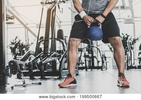 Close up legs of athlete exercising with kettlebell in comfortable keep-fit studio. Copy space in left side
