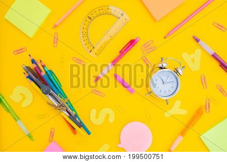 back to school or office styed pattern scene with multicolored school supplies on yellow