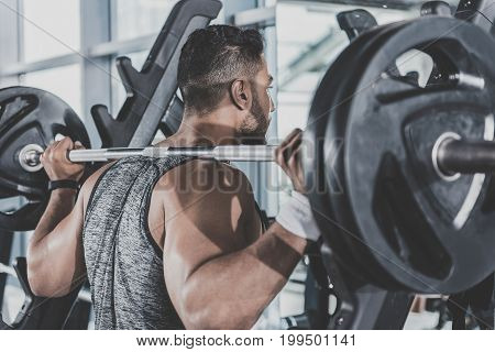 Serious bearded athlete pumping iron in fitness center. He turning back to camera. Sport concept
