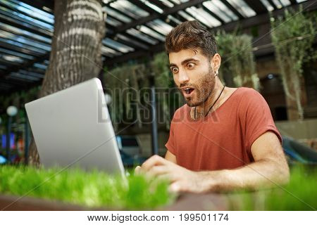 Shot of shocked bearded young man with dark hair and popped eyes, opened mouth dressed in red t-shirt looking at the screen of his notebook recieving e-mail with important news.