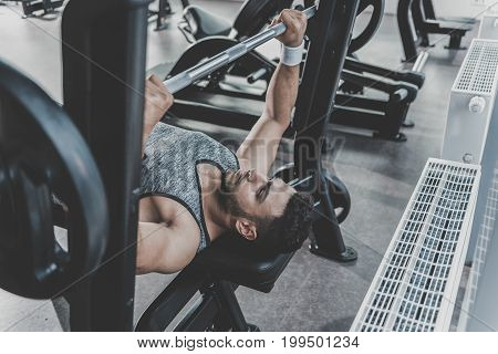 Top view bearded athlete demonstrating calmness while doing barbell bench press in comfortable fitness club. Copy space
