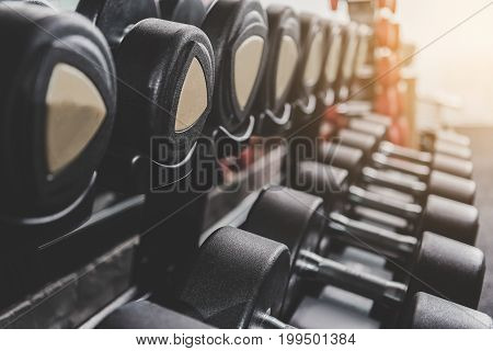 Close up black hard iron dumbbells locating on special shelves in rows for using them in keep-fit studio