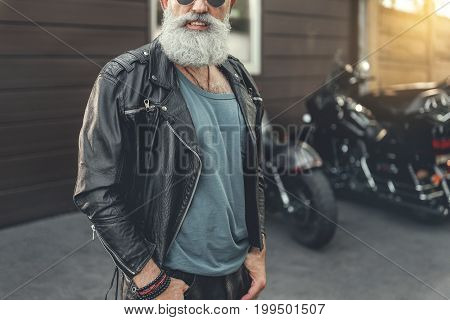 Hilarious bearded old biker in glasses is wearing leather. He standing nearby garage with vehicle. Portrait