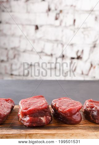 Raw filet mignon steaks closeup. Slices of fresh beef meat arranged in a row on wooden cutting board at gray background with copy space on white brick wall. Organic ingredients for restaurant meals