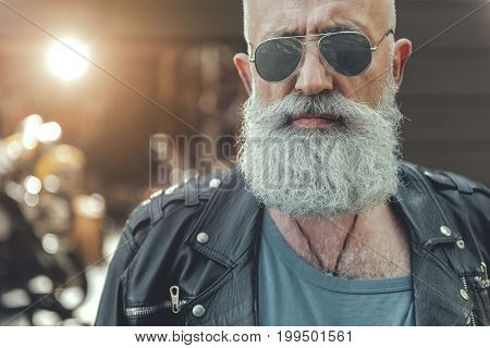 Happy old biker in sunglasses is standing near motorbikes. He wearing leather jacket and looking at camera with confidence. Portrait