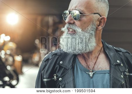 Confident old male person is wearing sunglasses and leather jacket. He looking at camera with seriousness. Portrait
