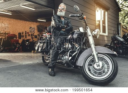 Confident old bearded biker in goggles is sitting at motorbike and crossing hands. He wearing leather clothes. Low angle