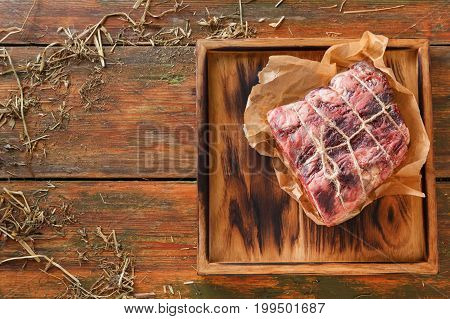 Raw black angus beef bound with rope in craft paper on cutting board. Aged prime marble meat at rustic wood background, top view, copy space