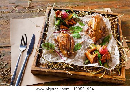 Excuisite restaurant food. Quails baked to golden crust with asparagus and chanterelles on grungy wooden platter, cutlery on craft paper. Fresh organic meals on rustic background, copy space, top view