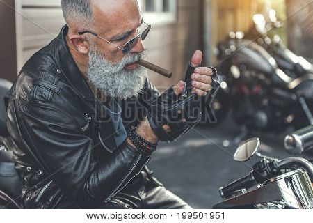Elder bearded man is wearing leather clothes and sitting on motorbike. He going to light cigar