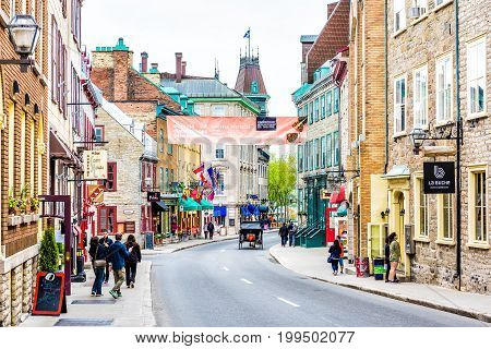 Quebec City Canada - May 29 2017: People walking on Saint Louis street by restaurants in old town road with banner