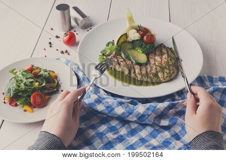 Lunch at restaurant. Grilled black angus beefsteak with steamed vegetables in fennel and green bell pepper sauce. Woman dining at nicely served white wooden table with checkered cloth, pov