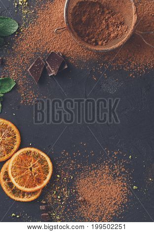 Tasty chocolate background. Cocoa powder in a sieve and sprinkled on surface, orange citrons and mint leaves on black slate. Top view, copy space