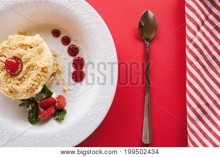Napoleon cake serving on red background. Sweet dessert on plate with decoration from strawberry, cherry and mint, close up top view, free space on right