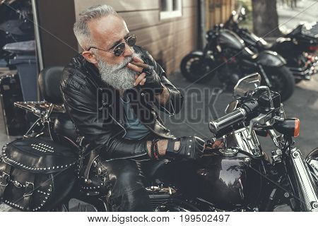 Aged bearded biker is smoking cigar and glancing ahead. He using polished motorcycle. Portrait
