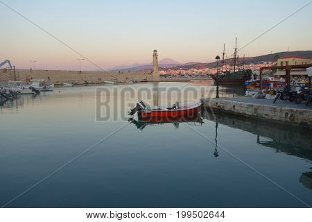 Red boat and summer evening in the Old Port in Rethymnon Greece
