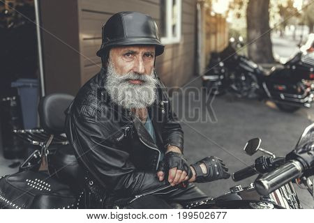 Attentive aged bearded biker is sitting on motorbike and looking at camera. He wearing clothes made of leather. Portrait